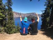 Boys with arms up in front of Crater Lake